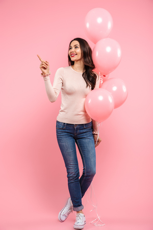 Full length photo of happy woman with long brown hair posing with lots of balloons in hand and pointing finger aside isolated over pink background Stock Photo