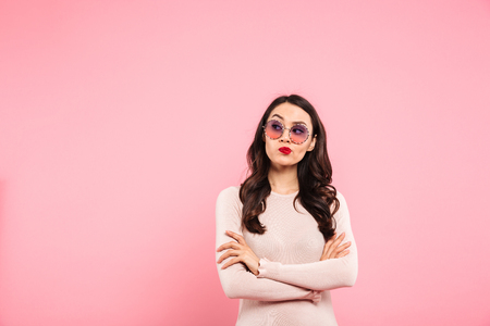 Photo of thoughtful adult girl with red lips wearing trendy sunglasses looking aside on copy space with interest isolated over pink background