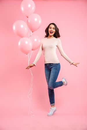 Full length image of wonderful woman 20s in casual clothing looking on camera with delight while holding bunch of air balloons in hand isolated over pink background