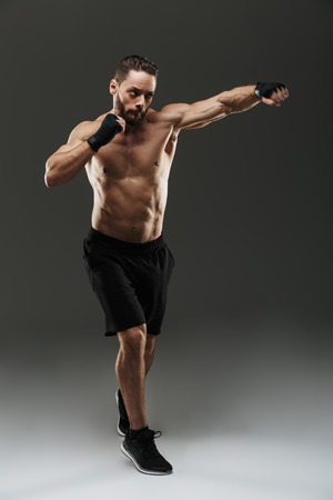 Full length portrait of a motivated muscular sportsman boxing over gray background