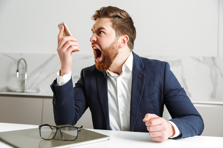 Portrait of an angry young businessman dressed in suit yelling at mobile phone while sitting at the table indoors Stok Fotoğraf