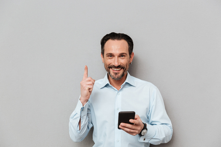 Portrait of a satisfied mature man dressed in shirt holding mobile phone and pointing finger up over gray background