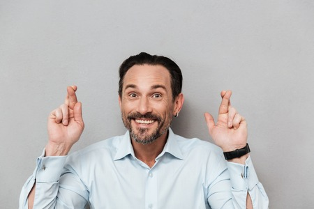 Portrait of a smiling mature man dressed in shirt holding fingers crossed for good luck over gray background Stock Photo