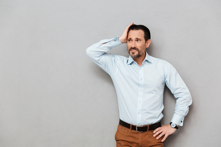 Portrait of a pensive mature man dressed in shirt looking away at copy space over gray background