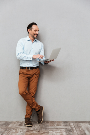 Full length portrait of a smiling mature man dressed in shirt using laptop computer while standing over gray background Stockfoto