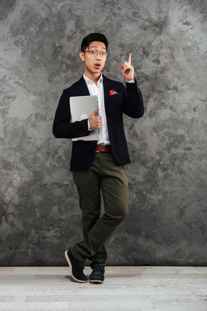 Full length portrait of an excited young asian man dressed in suit pointing finger away up copy space while holding laptop computer over gray background