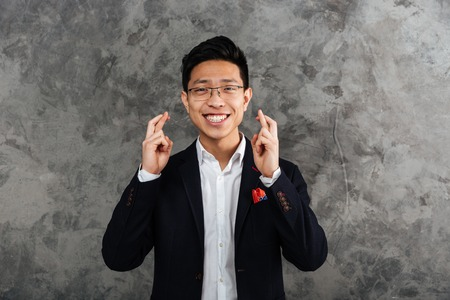 Portrait of a cheerful young asian man dressed in suit holding fingers crossed for good luck over gray background