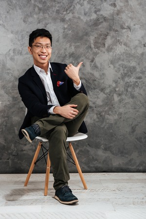 Full length portrait of a satisfied young asian man dressed in suit sitting in a chair and pointing finger away over gray background Banco de Imagens