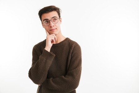 Close up portrait of a pensive young man in sweater looking away at copy space isolated over white background