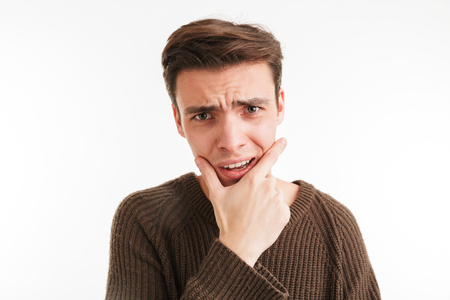 Close up portrait of a shocked young man in sweater looking at camera isolated over white background Stock Photo
