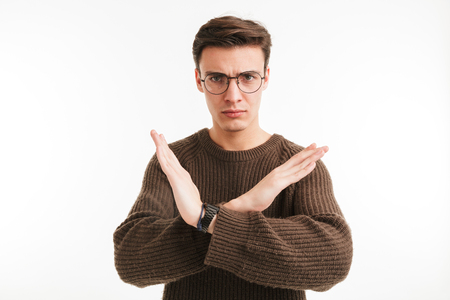 Portrait of a smiling young man in sweater showing crossed hands gesture isolated over white background