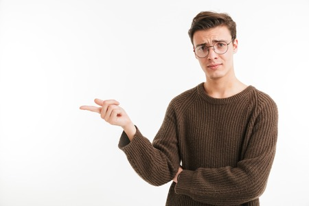 Portrait of a confused young man in sweater pointing finger away at copy space isolated over white background