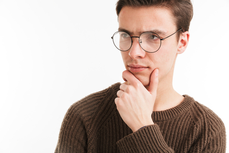Close up portrait of a pensive young man in sweater looking away isolated over white background Stock Photo