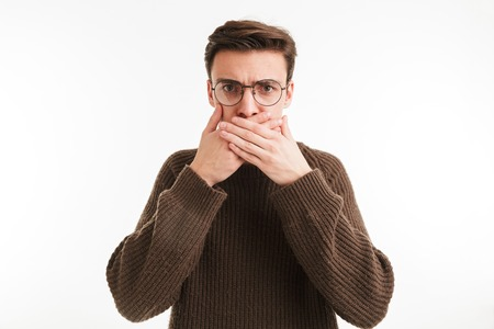 Portrait of a serious young man in sweater covering mouth with hands isolated over white background