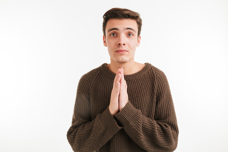 Close up portrait of a young man in sweater begging for something and looking at camera isolated over white background Stok Fotoğraf