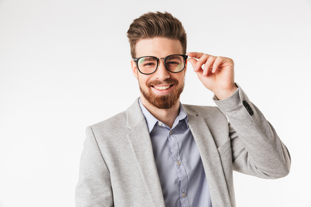 Portrait of a happy young man dressed in shirt and jacket wearing eyeglasses isolated over white background