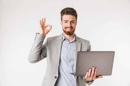 Portrait of a happy young man dressed in shirt and jacket holding laptop computer and showing ok gesture isolated over white background Stock Photo