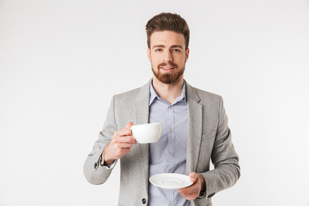 Portrait of a charming young man dressed in shirt and jacket holding cup with a saucer isolated over white background Stok Fotoğraf