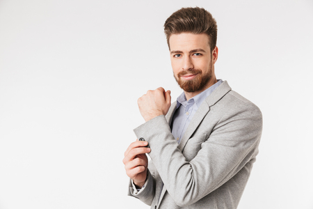 Portrait of a handsome young man buttoning his jacket and looking at camera isolated over white background