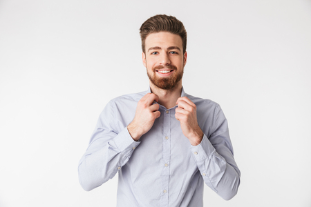 Portrait of a charming young man buttoning his shirt isolated over white background Foto de archivo