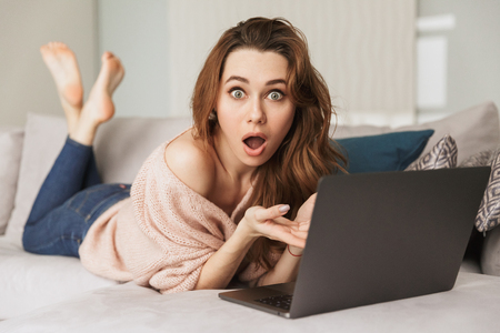 Portrait of a confused young woman using laptop computer while lying on a couch at home