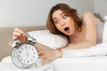 Image of frustrated woman waking up and being late turning off ringing alarm clock in panic