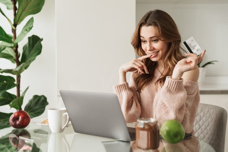 Portrait of a pretty young woman holding credit card while sitting with laptop computer at the table at home
