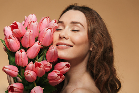 Beauty portrait of a pretty young topless woman with brown curly hair holding floers with eyes closed isolated over beige background