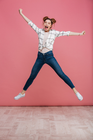 Full length portrait of a happy young girl celebrating success while jumping isolated over pink background