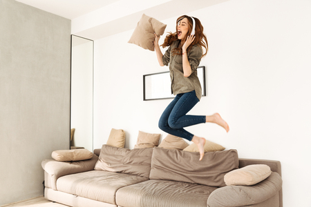 Joyful woman 20s in casual clothing playing around in cozy apartment and jumping on sofa while listening to music via wireless headphones 免版税图像