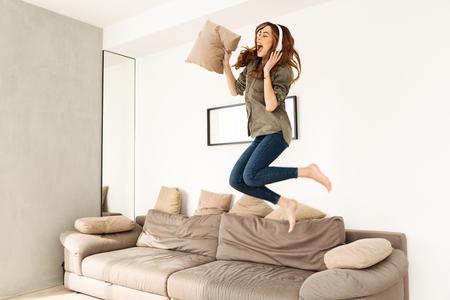 Radosna kobieta po dwudziestce w swobodnym ubraniu bawiąca się w przytulnym mieszkaniu i skacząca na kanapie, słuchając muzyki przez słuchawki bezprzewodowe
