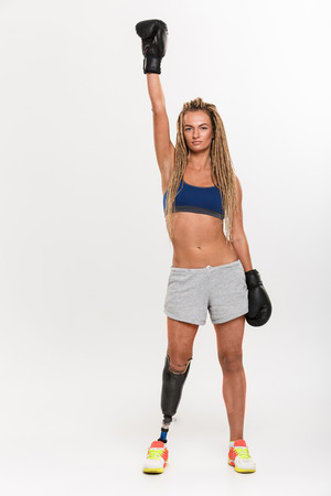 Picture of young disabled sports woman boxer with prosthesis standing isolated over white background wearing boxing gloves. Looking camera.