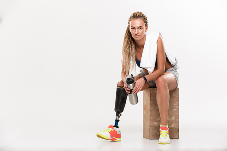 Portrait of a pretty young disabled sportswoman with leg prosthesis sitting with water bottle and looking at camera isolated over white background