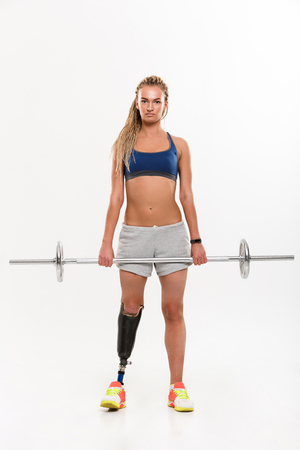 Image of young disabled sports woman with prosthesis isolated over white background. Looking camera make exercise with barbell. Stock Photo