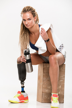 Portrait of a confident young disabled sportswoman with leg prosthesis sitting with water bottle and looking at camera isolated over white background