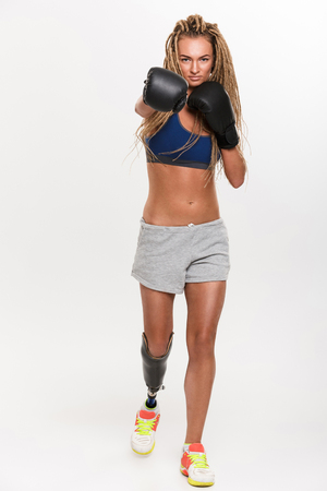 Full length portrait of a motivated young disabled sportswoman with leg prosthesis standing and boxing isolated over white background Stock Photo