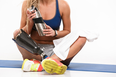 Cropped image of a young disabled sportswoman with leg prosthesis sitting on a mat with water bottle isolated over white background