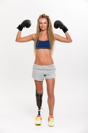 Full length portrait of a confident young disabled sportswoman with leg prosthesis wearing boxing gloves and showing biceps isolated over white background