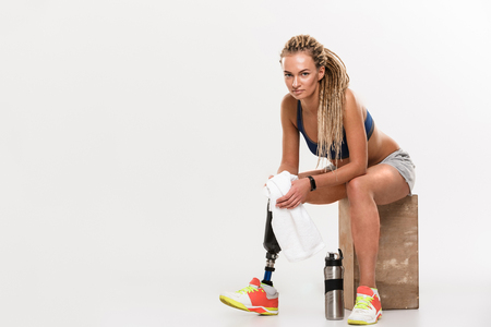 Photo of young strong disabled sports woman with prosthesis sitting isolated over white background. Looking camera holding towel.