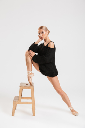 Picture of pretty serious young woman ballerina near stool over white wall background isolated. Looking camera.