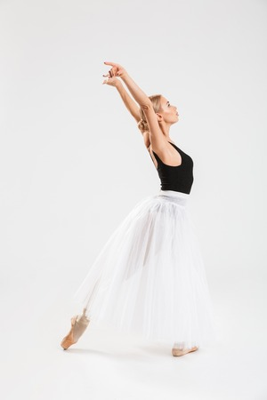 Full-lenght portrait of talented young woman ballerina dancing gracefully over white wall background isolated.