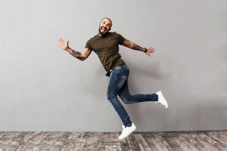 Full-length image of smiling guy with tattoo on his arms having fun while posing on camera isolated over gray background