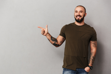 Image of unshaved joyful guy with tattoos on hands posing at camera and pointing finger aside on copyspace isolated over gray background