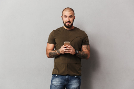 Unshaved man 30s in casual clothes looking on camera while using smartphone holding in hand isolated over gray background