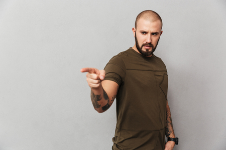 Unshaved serious guy with tattoos on hands posing at camera and pointing finger aside on copyspace isolated over gray background