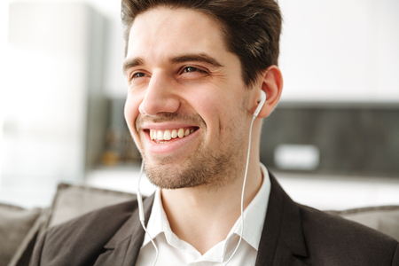 Photo of cheerful young businessman in home indoors listening music with earphones. Stock Photo