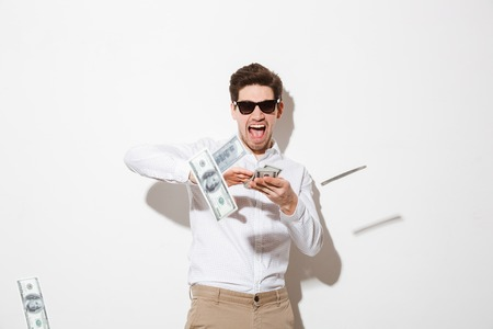 Portrait of a happy young man in sunglasses throwing money banknotes at camera isolated over white background Stockfoto