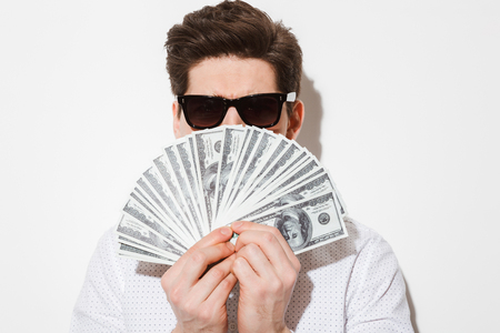Closeup picture of stylish guy in casual shirt and sunglasses covering his face with lots of money dollar bills isolated over white wall with shadow Stock Photo