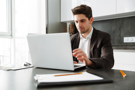 Photo of serious young businessman working indoors. Looking aside using laptop computer.