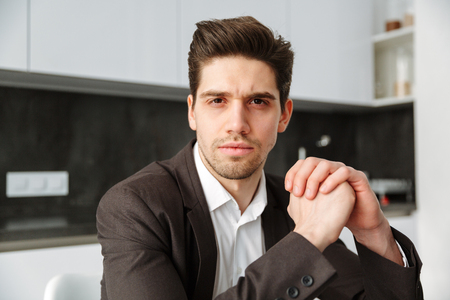 Photo of serious young businessman working indoors. Looking camera. Stock Photo